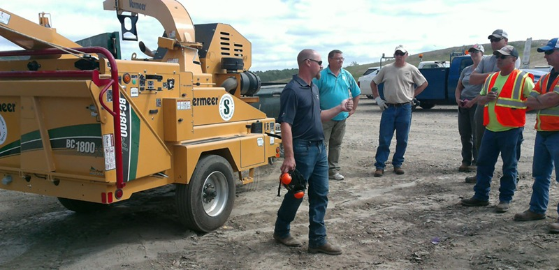 The SCISWA team learns how to operate the new wood chipper, which it will rent to communities within its service area.